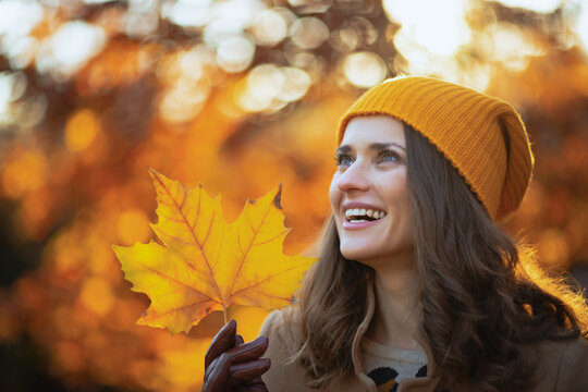 happy woman in brown coat and yellow hat