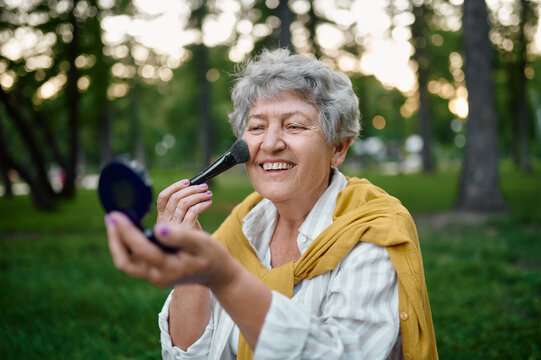 Pretty granny does makeup in park, back to yout