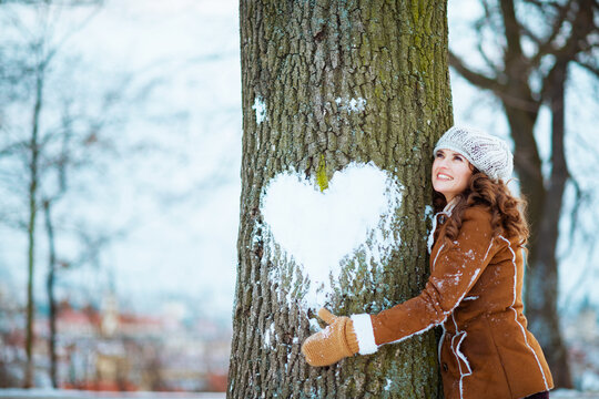smiling stylish woman hugging tree with snowy heart