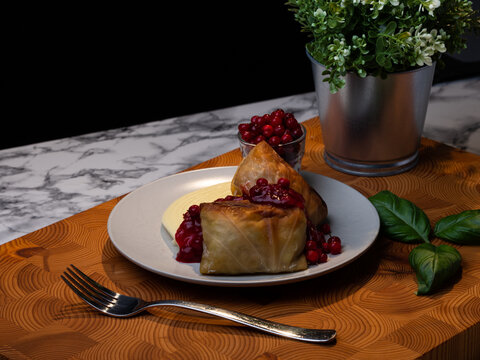 Traditional Finnish cuisines; closeup of a plate of cabbage rolls with mashed potatoes and lingonberry jam.