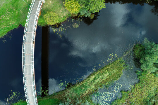Arching bridge over a deep blue river in greenery