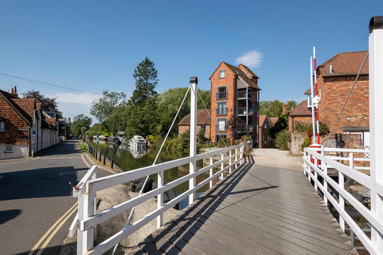 Newbury, Berkshire, England, UK. 2021.  White wooden swing bridge over the Kennet and Avon Canal at Newbury, tall buildings a former granary. UK