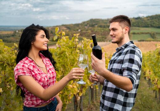 Man holding bottle of vine in vineyard, giving it yo beautiful gitl to taste it
