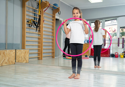 Cute Caucasian girl with hula hoop in the gym, smiling