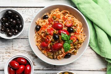 Obraz Bowl of tasty Pasta Puttanesca and ingredients on white wooden background - fototapety do salonu