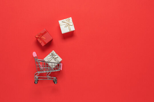 Shopping cart with gift boxes on a red paper background. Top view, flat lay. Holidays concept.