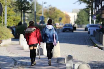 Fototapeta Dwie kobiety, dziewczyny spacerują po chodniku, deptaku w mieście.  obraz