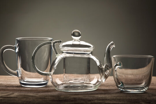 glass teapot and cup of tea on a wooden table