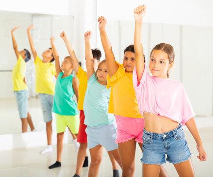 Smiling children primary school age rehearsing movements of ballet dance in modern studio