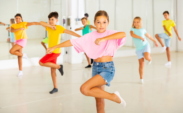 Young girls and boys performing dance in studio during rehearsal.