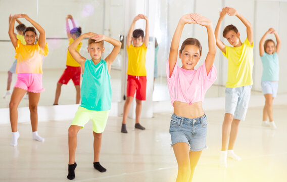 Group of children are learning dance moves in a modern studio