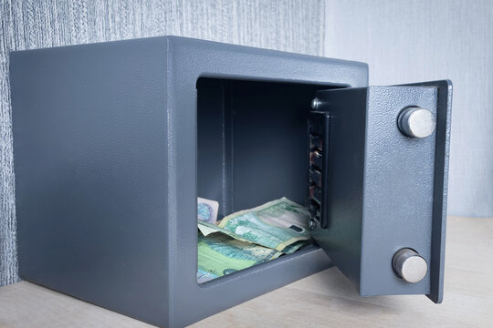 Close-up of a metal safe with an open door for storing money and documents.