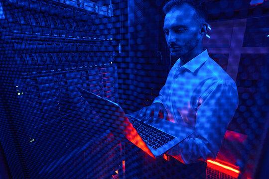 Server technician doing rack examination with laptop