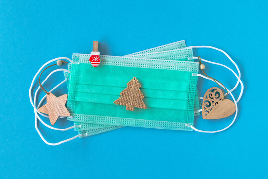 Wooden Christmas decorations and disposable medical face masks on blue background, flat lay. Concept for winter holidays in pandemic of coronavirus.