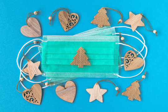 Craft wooden Christmas decorations and disposable medical face masks on blue background, flat lay. Concept for winter holidays in pandemic of coronavirus.