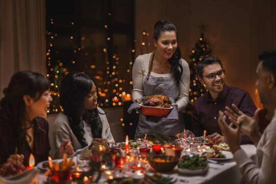 holidays and celebration concept - multiethnic group of happy friends having christmas dinner at home