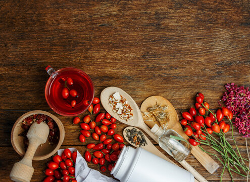 Dog rose, bunch branch Rosehips, types Rosa canina hips, essential oil and hot herbal tea cup on wooden. Medicinal plants and herbs composition space for text