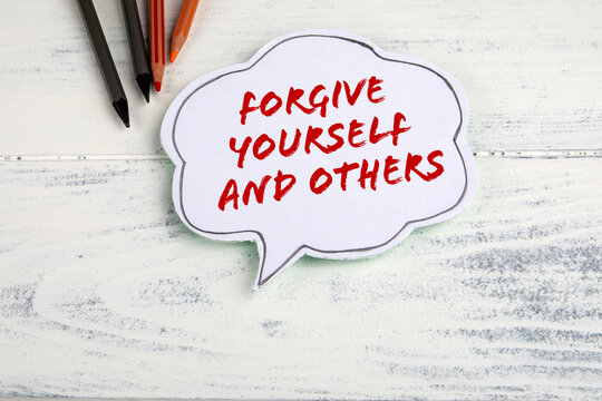 Forgive yourself and others. Speech bubble and pencils on a wooden background