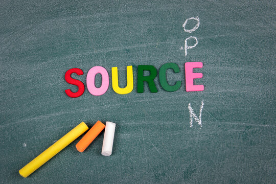 Open Source. Colored wooden letters and pieces of chalk on a green board