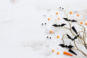 Fototapeta top view image of Halloween holoday. witcher broom, bare trees, treats and bats over white wooden table obraz
