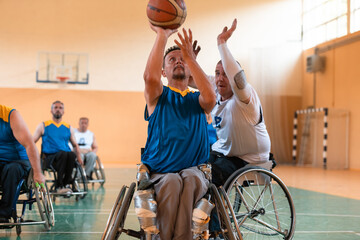 Obraz Disabled War veterans mixed race and age basketball teams in wheelchairs playing a training match in a sports gym hall. Handicapped people rehabilitation and inclusion concept - fototapety do salonu