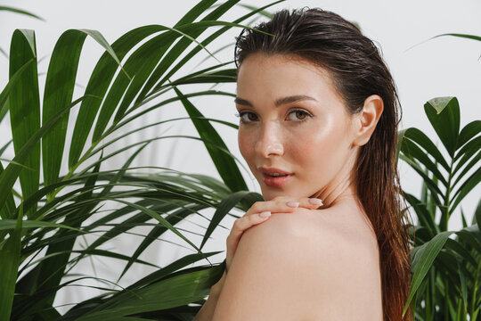 Young half-naked woman posing with plants on camera