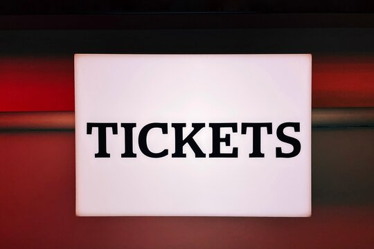 Illuminated sign for Tickets on the wall of a cinema