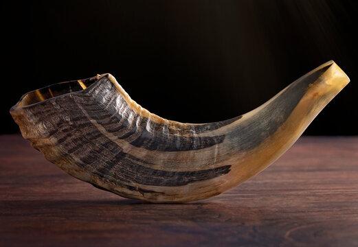 A Shofar Rams Horn on a Dark Wooden Table