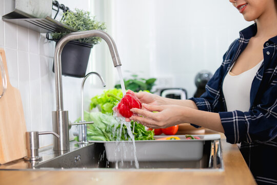 Close up Asian healthy woman washing vegetable above kitchen sink
