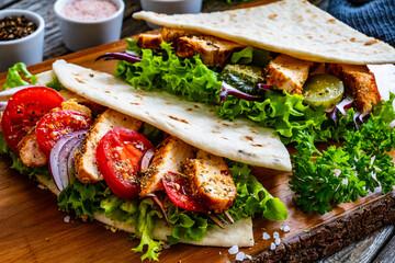Fototapeta Italian piada wraps - piadina stuffed with fresh vegetables and roast chicken breast  on wooden table  obraz