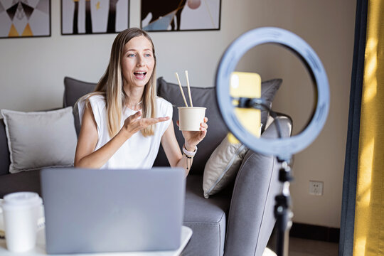 Young woman making photo or video content for social media with smartphone and light of ring lamp. Influencer Makes broadcast communicates with followers in social networks