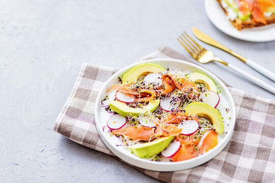 Flat lay top view of healthy salad with smoked salmon, avocado, radish and fresh microgreens alfalfa sprouts on white plate on gray concrete background. Healthy lifestyle. Growing sprouts. Green