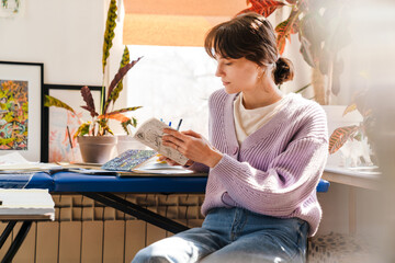 Obraz Young white woman looking into sketchbook while sitting indoors - fototapety do salonu