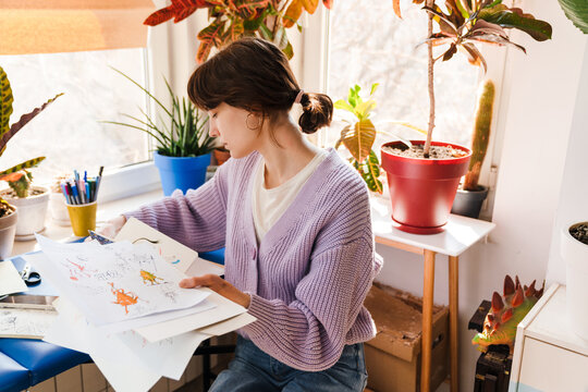Young white woman working with sketches while sitting indoors