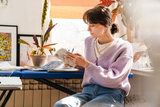 Young white woman looking into sketchbook while sitting indoors