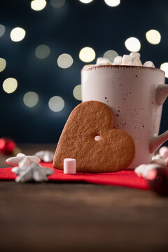 Large heart shaped holiday cookie leaning on a cup of hot cocoa with marshmallows