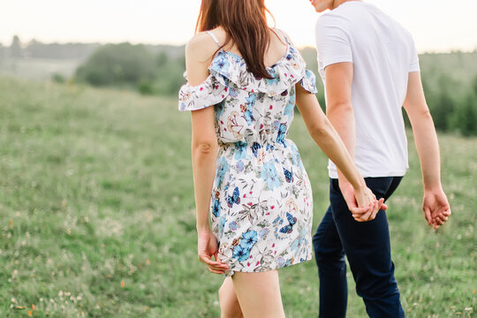 Young couple in love walking on through grass field. Walking along grass field.