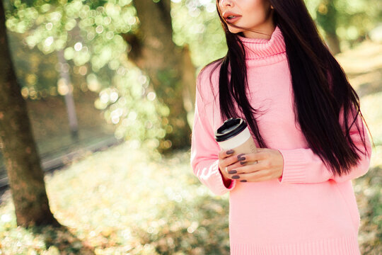 Beautiful woman drink coffee and walking in the park.