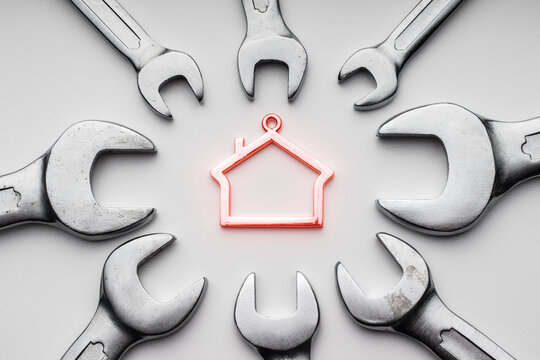 Wrenches around metal symbol of house. Repair and fix, home services, concept