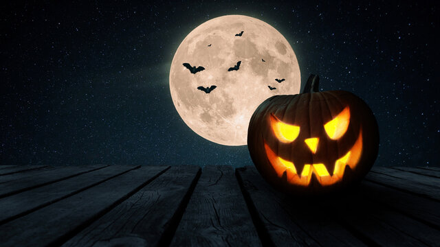 Halloween pumpkin stands on a wooden old table against the backdrop of the night sky with a full moon and bats. Happy halloween concept for design