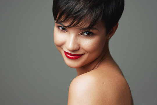 Portrait of beautiful young woman with short hair and red lipstick on her lips isolated on studio background
