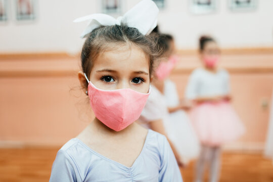 Group of beautiful little girls with protective face masks practicing ballet at dancing class. Coronavirus, Covid-19 concept.