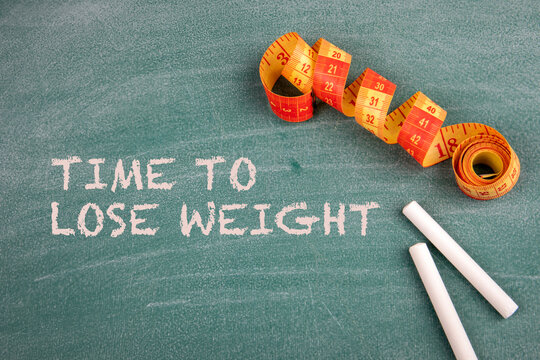 Time To Lose Weight. Tape measure and pieces of chalk on a blackboard