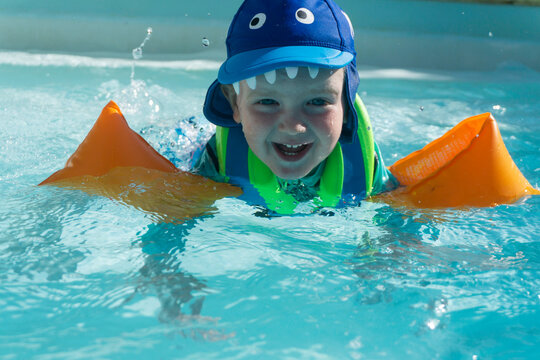 A two year old boy wearing arm bands splashes and plays in a swimming pool during summer