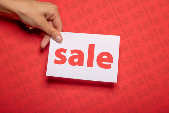 female hand holds a piece of paper with the inscription sale over strong red background cardboard with sale written on to promote special sales