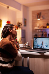 Fototapeta Sick woman talking to doctor on online video conference while sitting at home in festive kitchen. Unwell caucasian patient using telemedicine for prescription treatment and advice obraz
