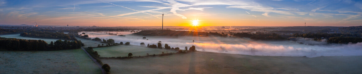 Fototapeta Sunrise and the first rays of sunshine over the fog-covered Ruhr meadows in Duisburg, Germany obraz