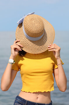 girl covers her face with straw hat at the sea in summer