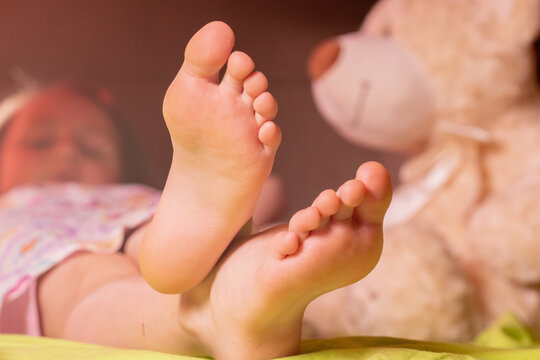 Bedtime concept. Cute child girl sleeping in the bed. Selective focus on groomed bare feet.