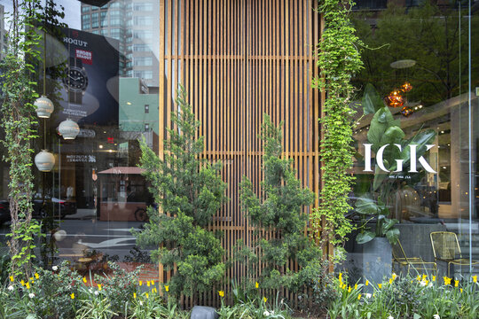 NEW YORK CITY, UNITED STATES - Apr 18, 2021: wooden striped wall with window display and plants. Reflection on a window